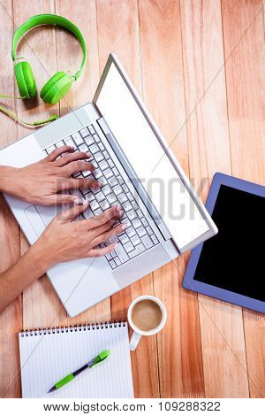 Overhead of feminine hands typing on laptop with stuff on desk
