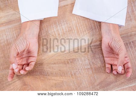 Close up view of hands in yoga pose on wood desk
