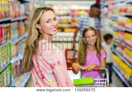 Smiling woman with her family at the supermarket