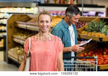 Portrait of a smiling woman at the supermarket with her husband