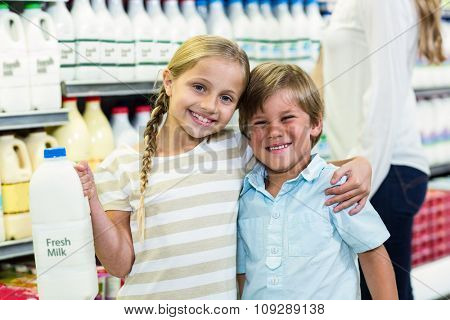 Smiling children holding milk and looking at the camera