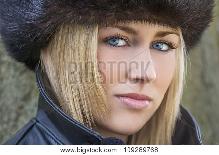Winter portrait of naturally beautiful woman in her twenties with blond hair, perfect teeth  and blue eyes wearing fur hat gloves and leather coat