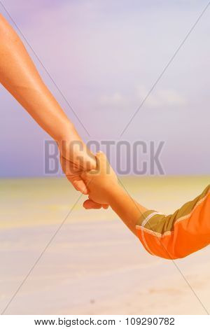 mother and child holding hands at the sea