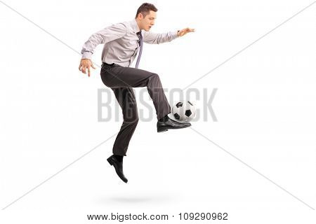 Full length profile shot of a young businessman playing football shot in mid-air isolated on white background