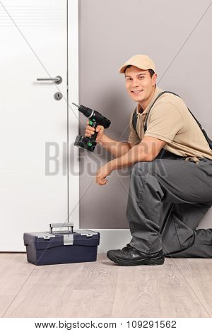 Vertical shot of a young worker installing a door with a screwing drill and looking at the camera