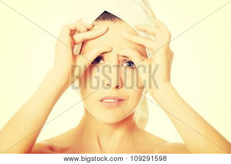 Young beautiful woman checking her wrinkles