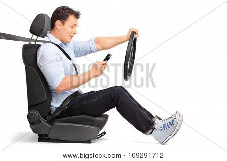 Studio shot of a young man driving a car and looking at his cell phone isolated on white background