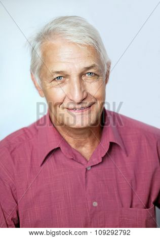 senior man  smiling relaxed,  portrait  on grey background