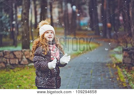 Cute Little Girl Stretches Her Hand To Catch Falling Snowflakes.