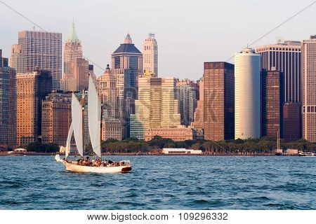 The lower Manhattan skyline in New York with a sailboat on the New York bay