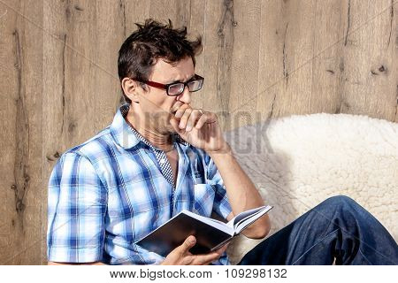 Man Yawning While Reading Literature On Couch