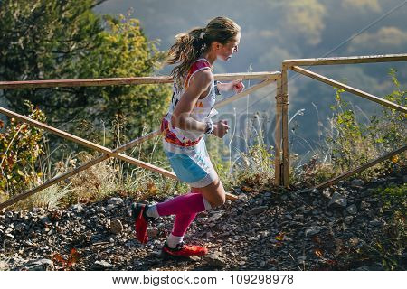 girl runner is running on a mountain trail. in background of mountain valley