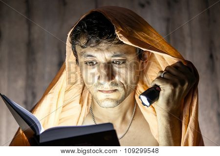 Man Reading Novel Book With Flashlight Under Blanket