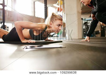 Fit Woman Doing Push Ups With Personal Trainer In Gym