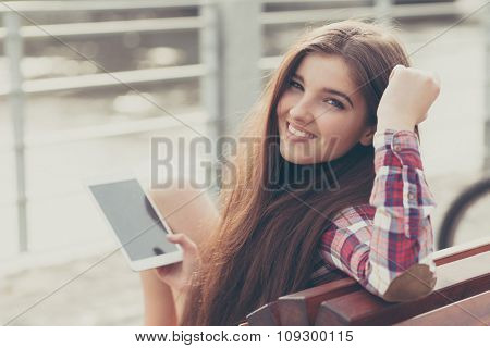 Face portrait of beautiful young woman using a tablet pc