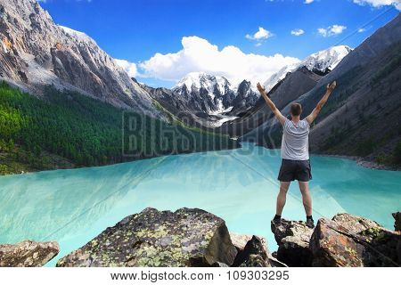 Hiker standing with raised hands near the beautiful mountain lake and enjoying valley view