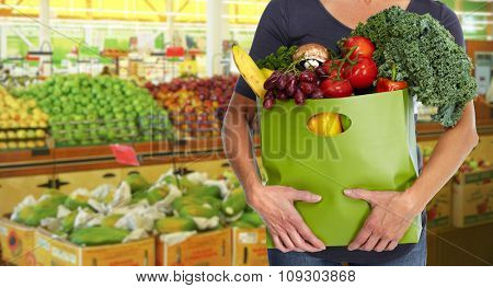 Woman with grocery bag of vegetables over store background.