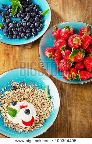 Berries And Muesli On A Wooden Table.