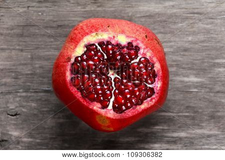 Slice  Pomegranate Fruits On Old Wooden Table.
