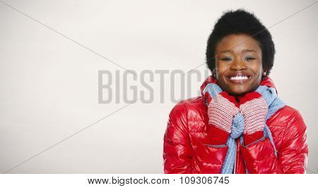 African -american woman in winter clothing over winter background.