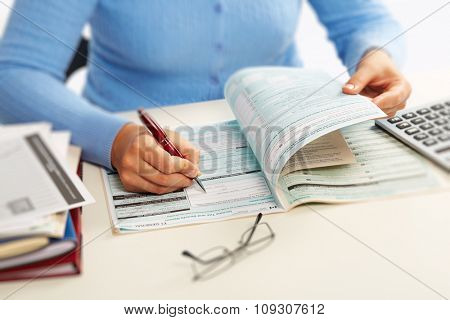 Hand with a pen writing. Accounting and finance background.