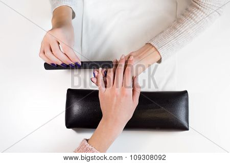Manicurist at work nail file hand little finger