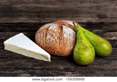 Fresh Bread With Pear And Cheese On Old Wooden Table
