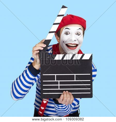 Emotional funny mime actor wearing sailor suit, red beret posing on color blue background.