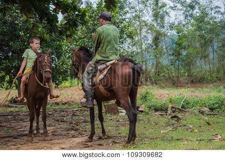 Vinales Valley, Cuba - September 24, 2015:  Local Cuban Coutryside Man And Hes Son Ride Horsback In