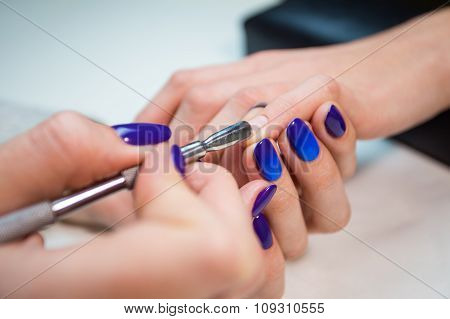 Manicurist removing cuticle from the girl nail