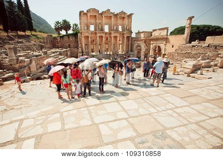 Tourists With Sun Umbrellas Standing Near Historical Celsus Library Of Ephesus City