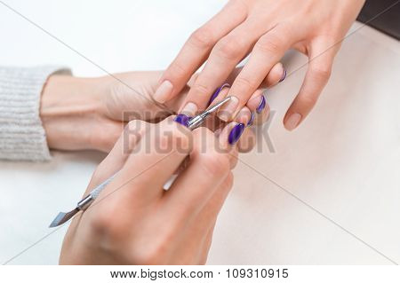 Top view manicurist removing cuticle from the nail