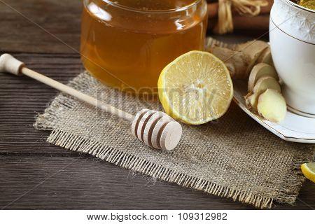 Golden honey with honeystick, lemon, tea and cinnamon on wooden table