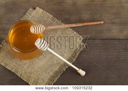 Golden honey with honeysticks on wooden table.