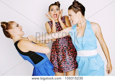 three elegant fashion woman fighting on white background, bright dresses