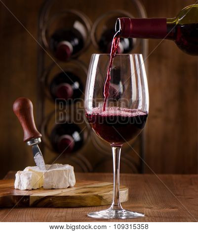 Red Wine Pouring Into Wine Glass On  Wooden Background.
