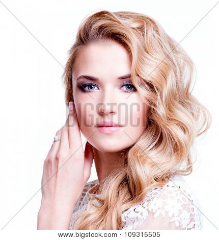 Portrait of beautiful caucasian woman with blond curly hair posing at studio.