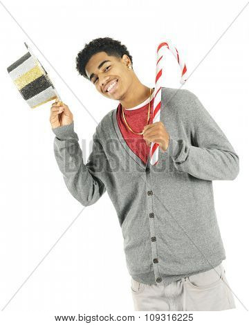 A tall teen boy holding a giant candy cane while tipping a New Year's Eve hat.  On a white background.
