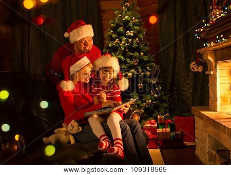 Family reading a book by a Christmas tree in cozy living room in winter