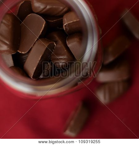 Chocolate Candies In Jar. Top View, Against Red Background, Close Up