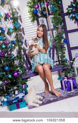Beautiful Girl In A Turquoise Dress Sitting On A Swing Next To A Christmas Tree, Toys And Gifts, Is