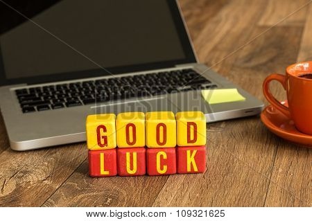 Good Luck written on a wooden cube in a office desk