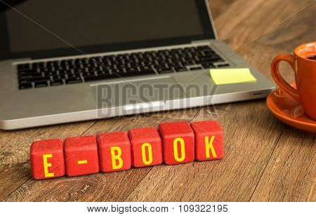 E-Book written on a wooden cube in a office desk