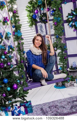 Charming Brunette In Jeans And A Blue Sweater Sits On A Swing On White Terrace Surrounded By Christm