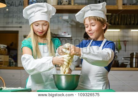 Funny happy chef boy width girl cooking at restaurant kitchen and knead the dough
