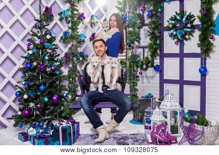 Couple In Love On A White Terrace Sits On The Swing Next To A Christmas Tree And Presents, Playing W