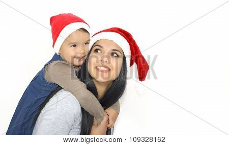 Christmas, Family, Childhood And People Concept - Happy Mother And Little Girl In Santa Hats Over Ho