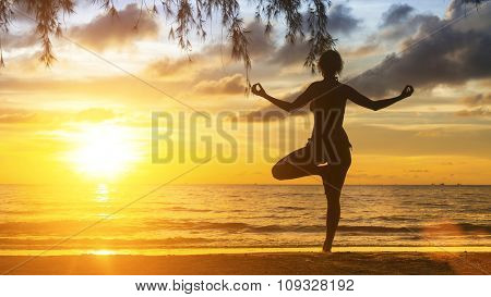 Silhouette of yoga woman standing on the beach during sunset.