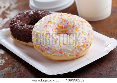 Donuts with frosting and sprinkles on a paper tray