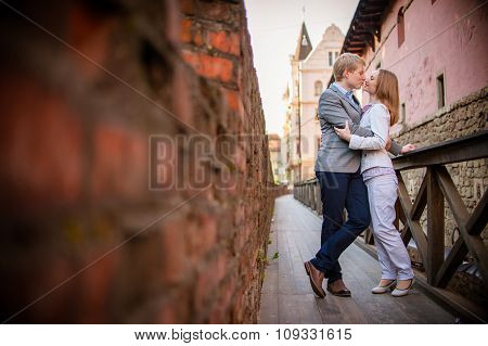 Pretty sunny outdoor portrait of young stylish couple while kiss